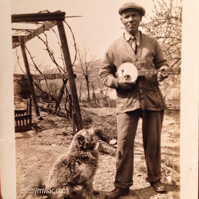Old photo of Italian man playing a banjo with a dog sitting at his feet